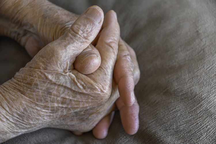 Cropped image of senior woman with hands clasped