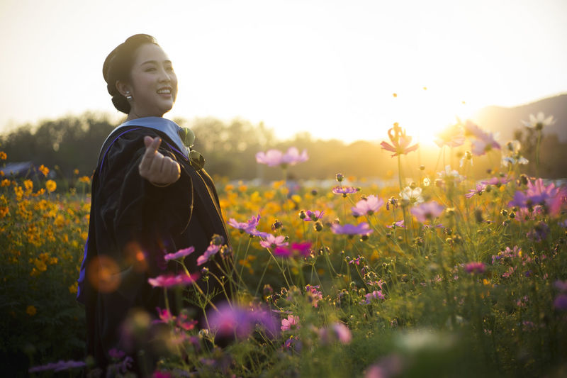 Beauty In Nature Clear Sky Cosmos Flower Day Field Flower Flower Head Flowerbed Freshness Growth Happiness Leisure Activity Lifestyles Nature One Person Outdoors Plant Real People Sky Standing Sunlight Sunset Yellow Young Adult Young Women