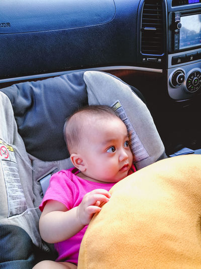 6 month old baby is resting in her car seat while playing with a donuts pillow and waiting for her big siblings in the car. Car Seat Baby Baby Girl Baby Sitting Car Car Interior Childhood Close-up Cute Day Infant Land Vehicle Lifestyles Mode Of Transport Pink Color Playing Real People Sitting Transportation Vehicle Seat