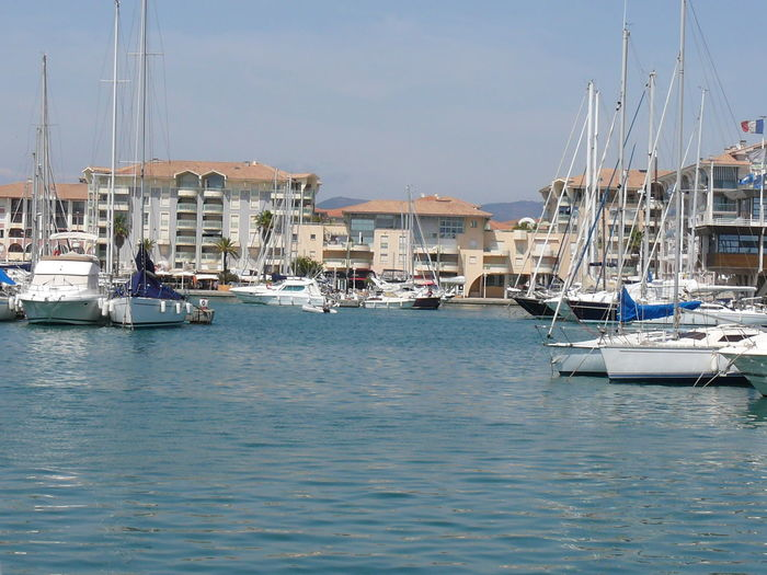 Boats moored at harbor by houses against sky