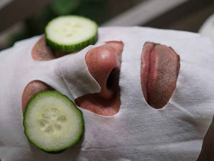 Close-Up Of Man With Cucumber And Facial Mask On Face