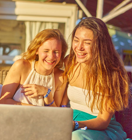 Bonding Casual Clothing Cheerful Communication Day Enjoyment Friendship Front View Fun Happiness Laptop Laughing Leisure Activity Outdoors Real People Sitting Smiling Technology Togetherness Two People Using Laptop Wireless Technology Young Adult Young Women Young Women Style