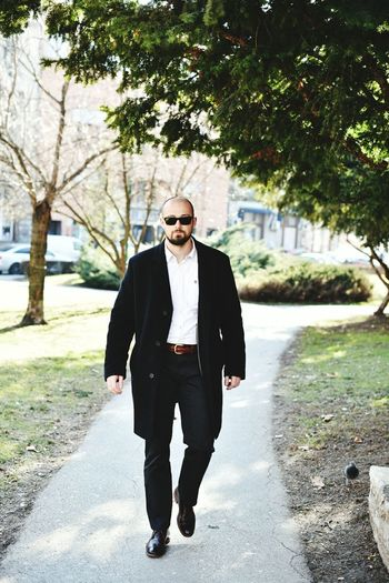 Businessman walking on footpath by tree