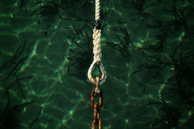 Close-up of rope connection with chain over lake