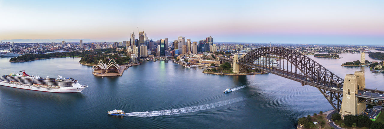 Panoramic view of Sydney city skyline during sunrise Architecture Built Structure Building Exterior City Transportation Nautical Vessel Water Cityscape Bridge Connection Bridge - Man Made Structure Building Sky Travel Destinations Mode Of Transportation River High Angle View Travel Office Building Exterior No People Skyscraper Outdoors Passenger Craft Financial District