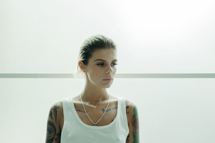 Young tattooed woman standing against wall