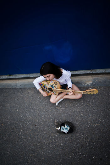 High angle view of young woman playing guitar by wall on street