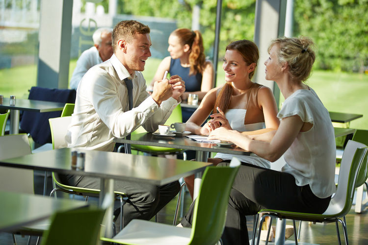 Friends Talking While Sitting In Restaurant