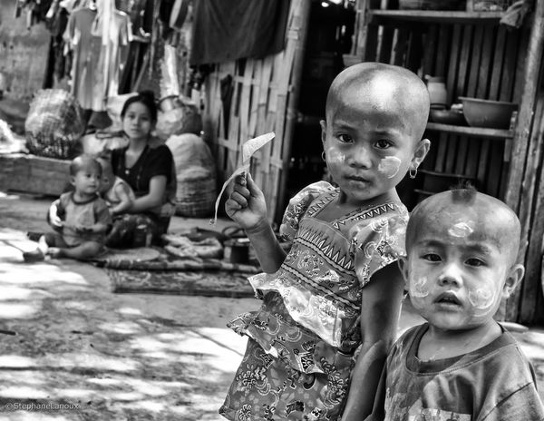 "Meet the Chin people, a forgotten community from Myanmar. Qualified by Human Rights Watch as the ""Forgotten People"", the Chin people are of Tibet-Mongolian origin. They probably came to Burma in the late ninth or tenth century A.D. During my trip in April, I had the opportunity to visit 4 villages long the Lemro river into the Rakhine red territory: Kheik Chaung, Sun Sway Jo, Pan Paung and Cho May villages. One particularity and ancient rite of this remote population are the women face tattoos. Meant to prevent invaders from stealing away the local women, young women were tattoed before the age of getting married. Tattooing took over a day to complete and was extremely painful, especially the eyelid area. Each area of Chin state has a distinct tattoo pattern, so it is actually possible to discern where a woman comes from by the pattern on her face. The practice is no longer permitted by the Burmese authorities, nor is the younger generation interested in partaking in the custom. Therefore, this part of Chin culture will soon be gone, so you witness here the last living generation and alive women who embrace this custom. Black And White Blackandwhite Built Structure Children Chilling Community Contrast Face Human Body Part Human Condition Human Face Human Representation Kids Myanmar Old Oppression Photography Photojournalism Poverty Rakhine State Tattoo Tattooed Travel"