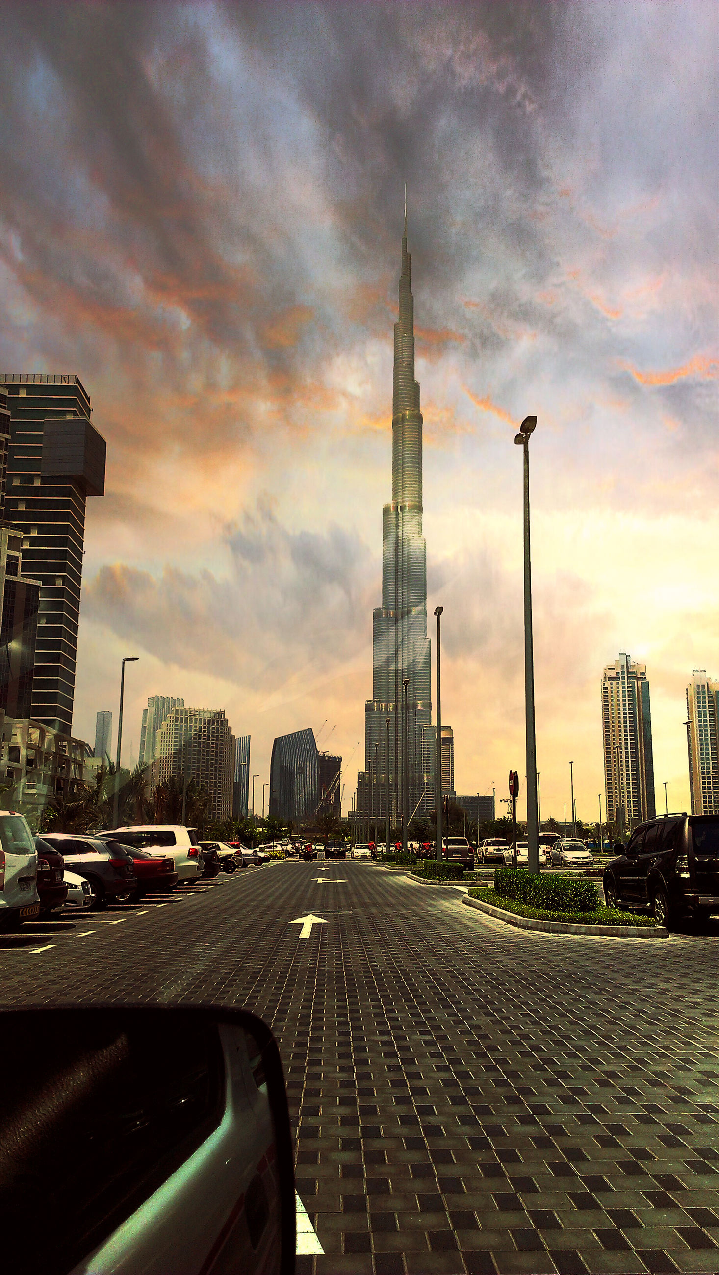 building exterior, architecture, city, built structure, sky, cloud - sky, transportation, tall - high, tower, skyscraper, car, sunset, cloudy, road, the way forward, street, land vehicle, mode of transport, capital cities, travel destinations
