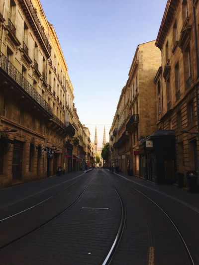 Empty road amidst buildings against clear sky