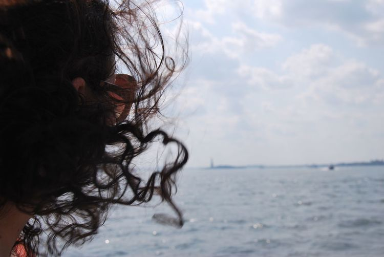 Portrait of woman by sea against sky