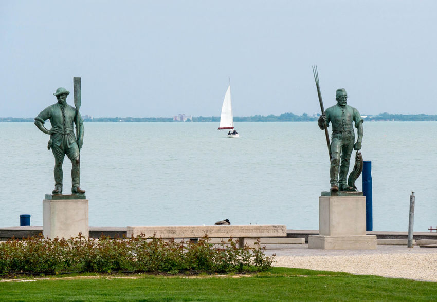 Sculptures of Fisher and Ferryman at the Lake Balaton in Hungary Calmness Ferryman Guards Lake Balaton Touristic Attraction Boat Bronze Statue Fisher Historic Horizon Horizon Over Water Human Representation Male Likeness Monument No People Outdoors Representation Sailboat Sailboats Sculpture Sky Statue Travel Water