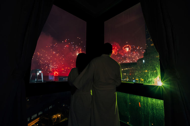 Rear view of man and woman looking firework display through window