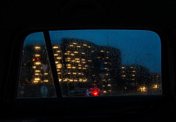 Illuminated cityscape seen through window at night
