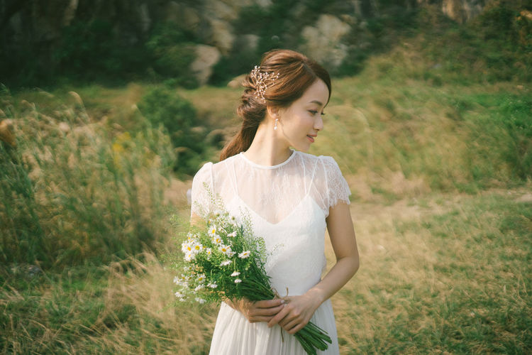 Bride holding flowers looking away while standing on grassy field