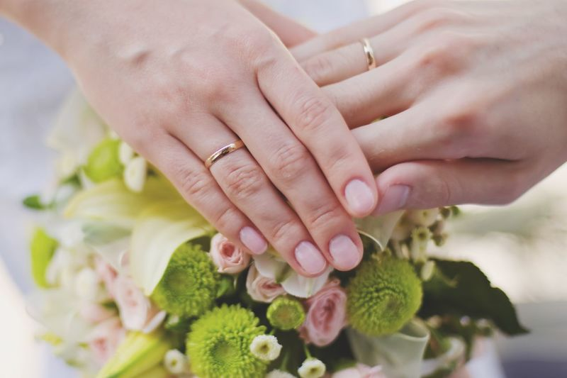 Cropped hands of bride wearing rings touching flowers