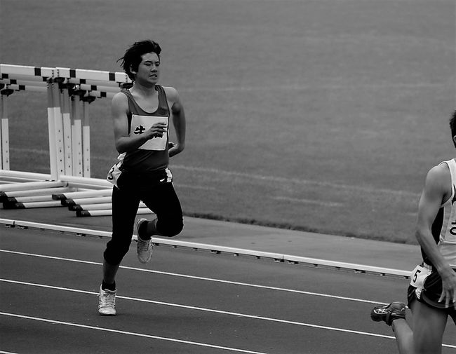 Full length of young man running on sports track