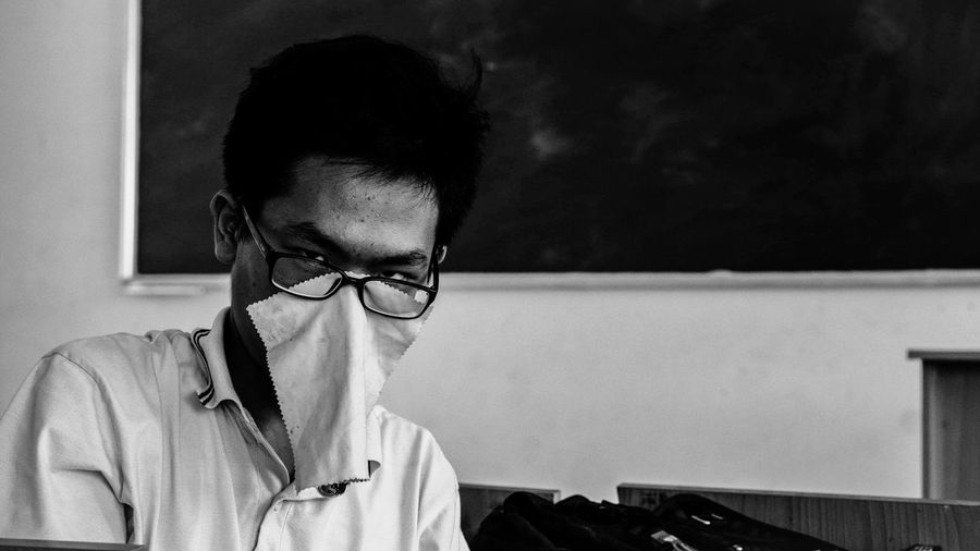 Portrait of teenage boy with fabric on face in classroom