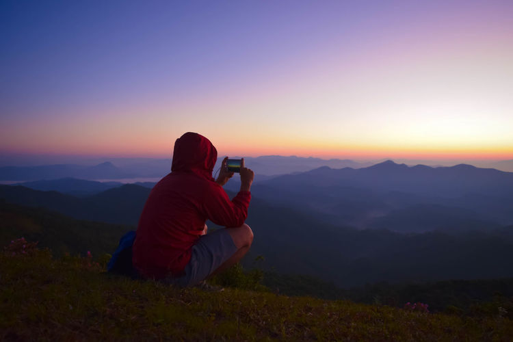 Rear view of man photographing on mountain during sunset
