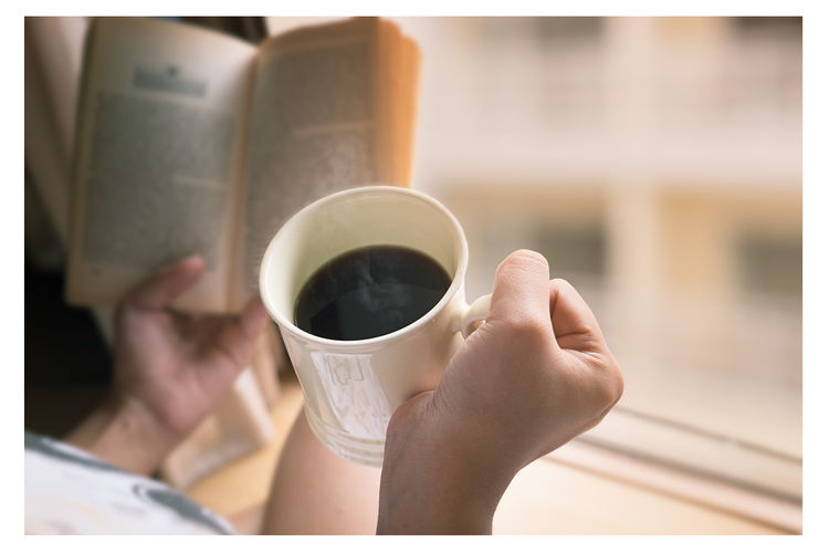 Cropped Image Of Woman Holding Black Coffee Cup And Book By Window At Home