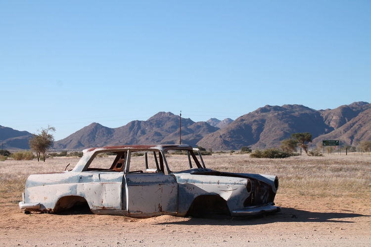 Abandoned car on landscape against clear blue sky