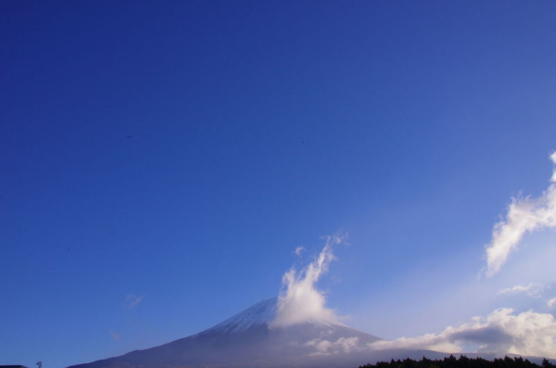 Low angle view of volcanic mountain against blue sky