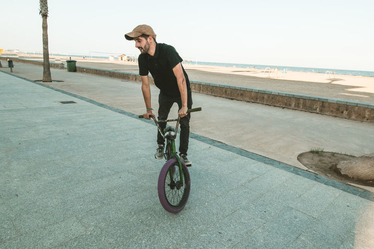 Man riding bicycle by sea against sky