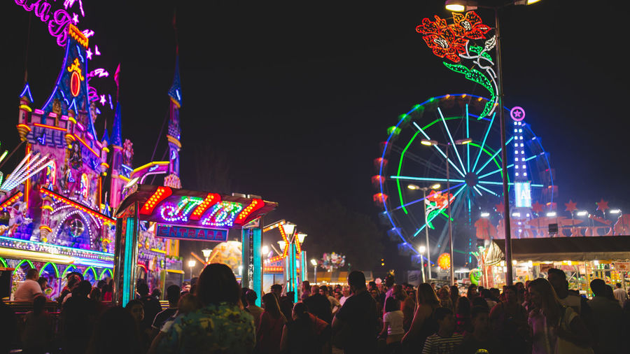 People in illuminated amusement park against sky at night