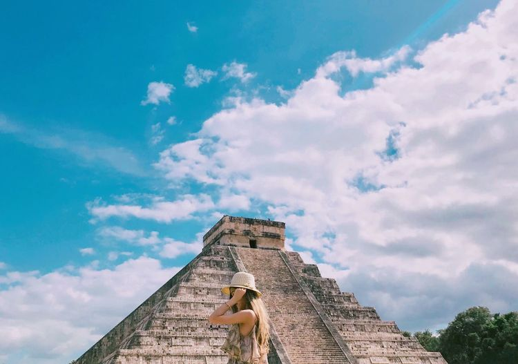 Low Angle View Of Young Woman Standing By Pyramid Against Cloudy Sky