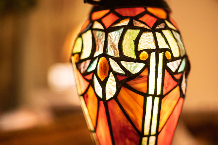 Focus On Foreground Close-up Art And Craft Creativity Indoors  No People Pattern Multi Colored Decoration Lighting Equipment Design Representation Craft Single Object Orange Color Illuminated Metal Selective Focus Glass - Material Human Representation Electric Lamp Floral Pattern