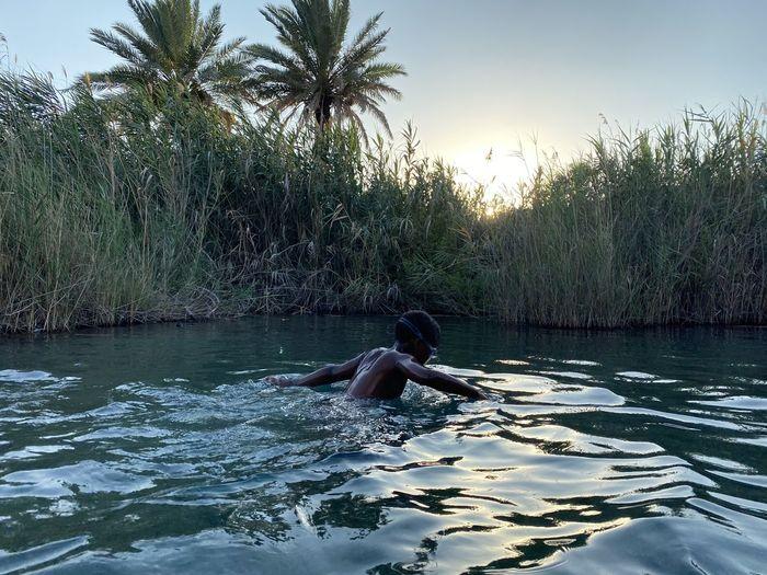 Man swimming in pool by lake against sky