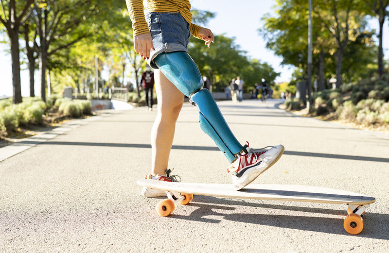 Low section of boy skateboarding on road
