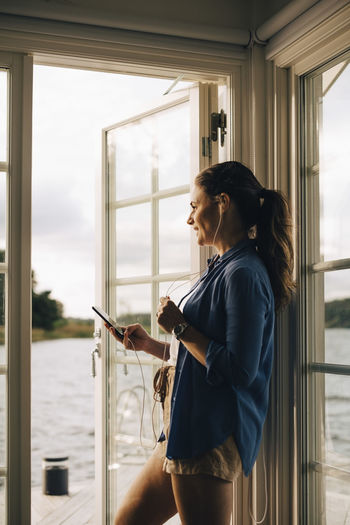 Side view of woman looking through mobile phone at window