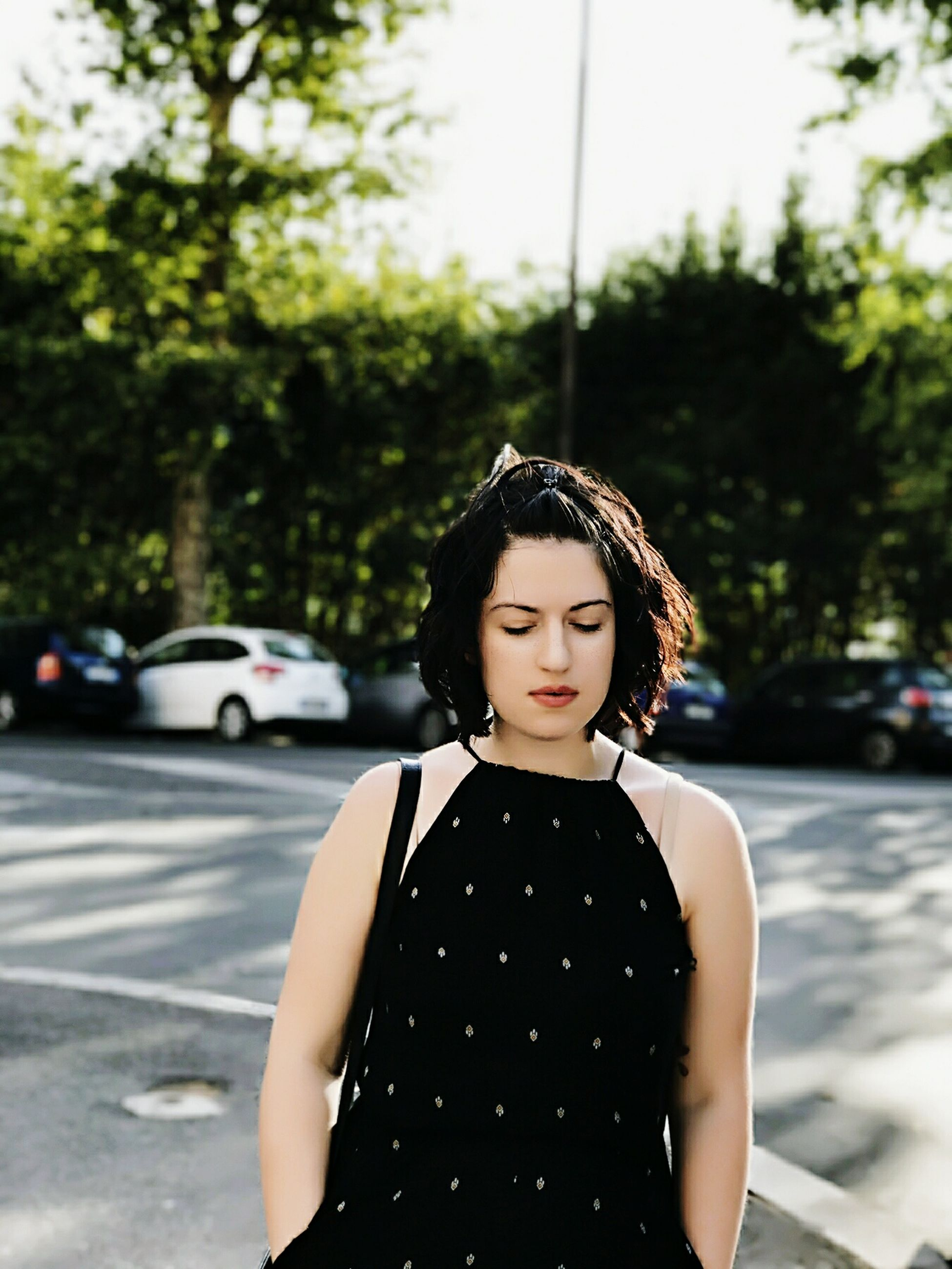 one person, young adult, outdoors, car, waist up, focus on foreground, young women, street, real people, day, front view, standing, transportation, road, tree, beautiful woman, nature, sky, people