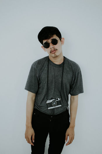 Portrait of young man wearing sunglasses standing against white background