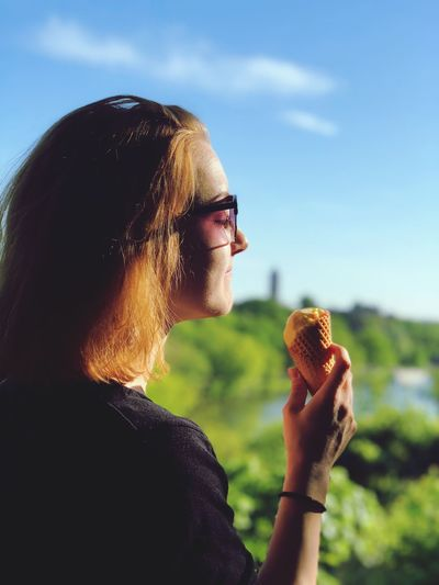 Side view of young woman eating ice cream cone while standing against blue sky