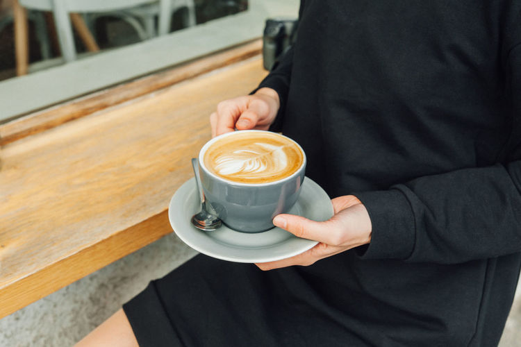 Midsection of man holding coffee cup at cafe