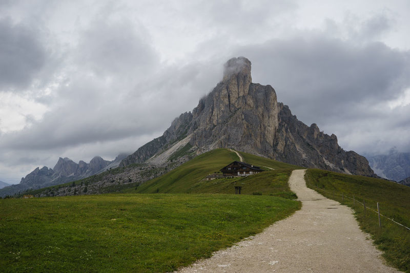 Day Grass Landscape Mountain Mountain Range Mountain Road Nature Outdoors Physical Geography Road Sky The Way Forward Alps Valley Field Peak Clouds Dolomites Passo Giau Italy Chalet No People