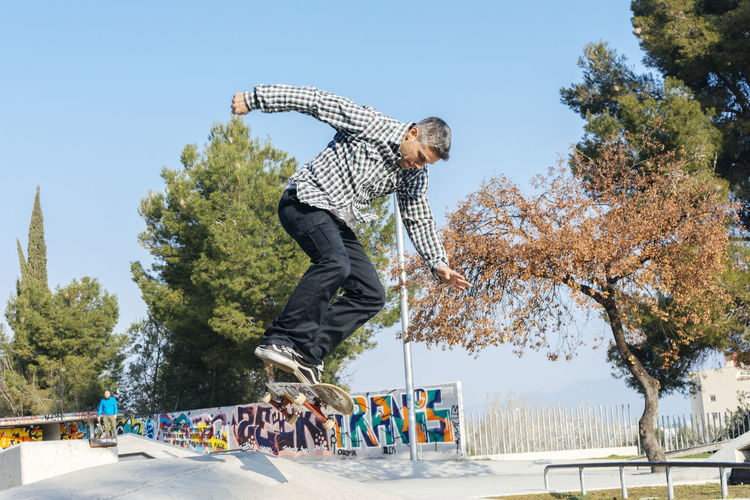 Skateboard Sport Men Casual Clothing Jumping Skate Skate Park Skateboard Park Tree Plant Real People Full Length Sky One Person Mid-air Day Leisure Activity Nature Lifestyles Skill  Motion Balance Enjoyment Outdoors
