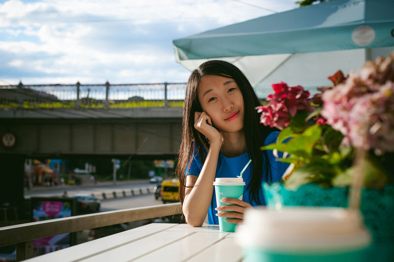 Portrait of woman having coffee while sitting at outdoor cafe