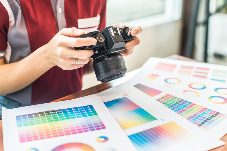 Midsection of design professional photographing color swatch on table