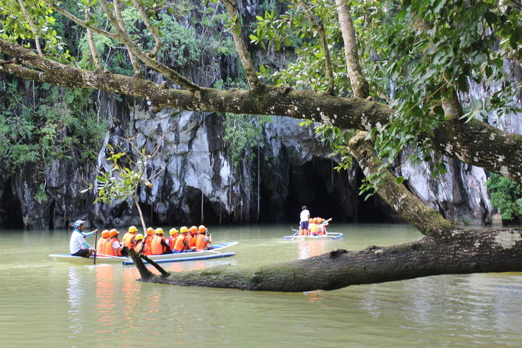 People in boat on river against trees