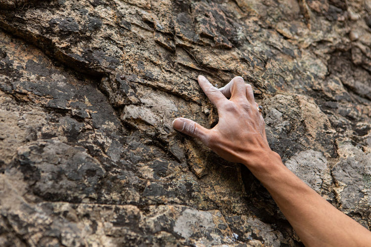 Midsection of human hand on rock