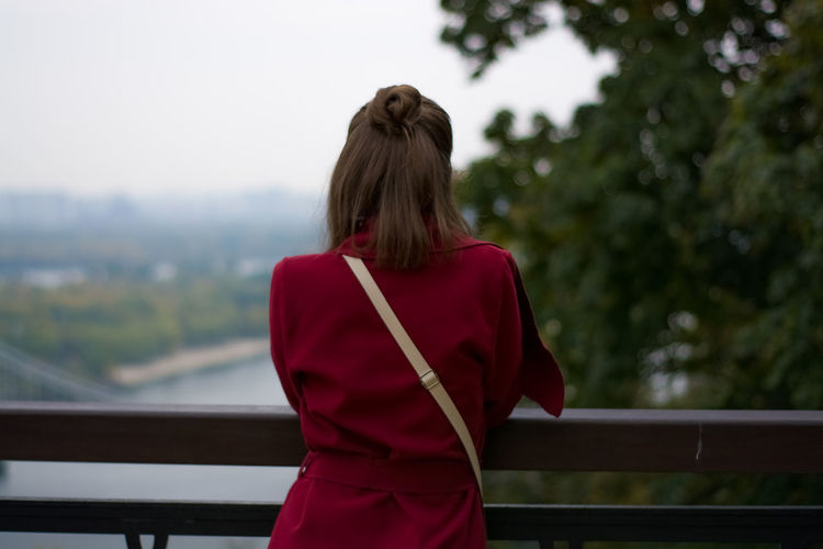 Rear view of woman standing at railing