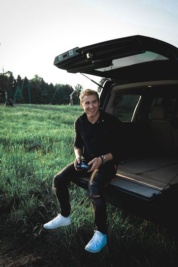 Young man smiling while sitting in car trunk on grassy field