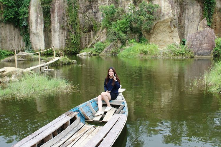 Woman sitting on boat in river