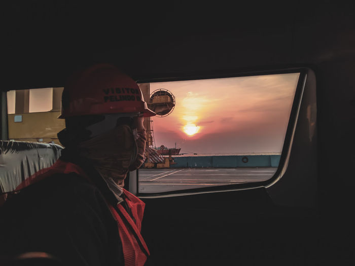 Portrait of man seen through car window during sunset