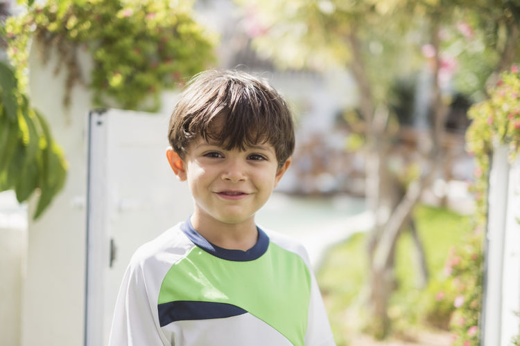 Portrait of smiling boy standing against trees