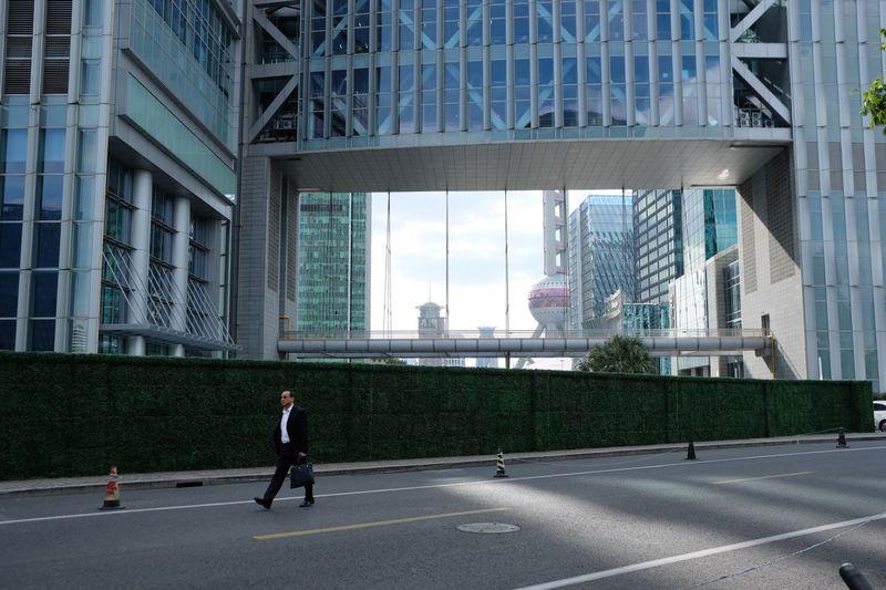 Man walking on street by modern buildings in city